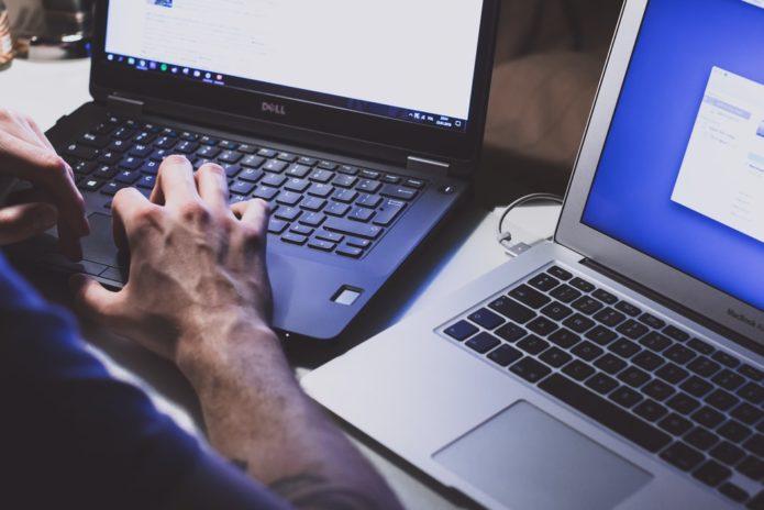 man using 2 laptops